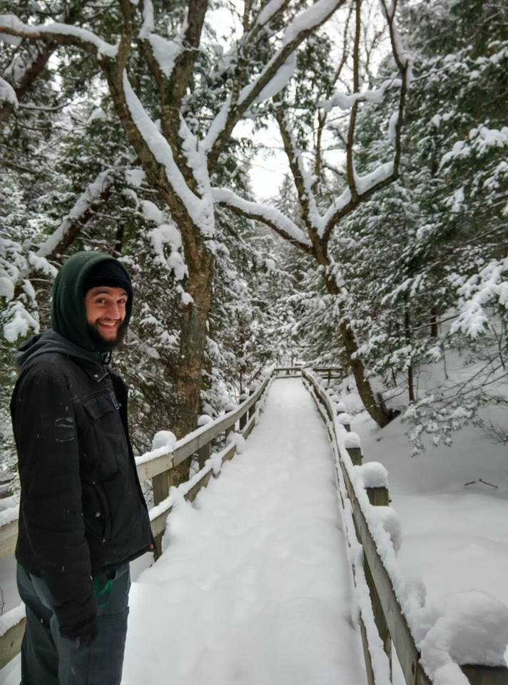 A picture of me standing on a path in a snow covered forest.